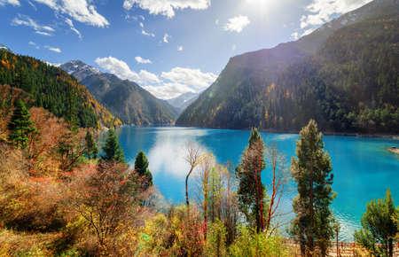 Fantastischer Blick auf den langen See mit azurblauem Wasser zwischen bunten Herbstwäldern und Bergen im Naturschutzgebiet Jiuzhaigou (Jiuzhai Valley National Park), China. Erstaunliche sonnige Herbstlandschaft.