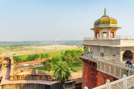 Fabulous view of the Musamman Burj in the Agra Fort, India. The Taj Mahal is visible in background. The octagonal tower with dome is a popular tourist attraction of South Asia. Mughal architecture.
