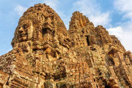 Awesome bottom view of ancient towers with mysterious giant stone faces of Bayon temple in Angkor Thom, Siem Reap, Cambodia. Angkor Thom is a popular tourist attraction of Asia.