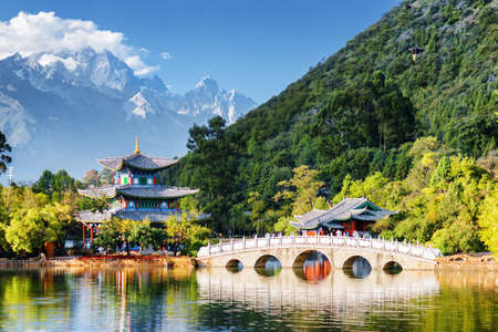 Scenic view of the Jade Dragon Snow Mountain and the Black Dragon Pool, Lijiang, Yunnan province, China. The Suocui Bridge over pond and the Moon Embracing Pavilion in the Jade Spring Park.