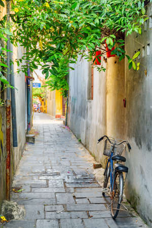 Bicycle parked near wall of house on scenic narrow street in Hoi An Ancient Town (Hoian), Vietnam. Hoi An Ancient Town is a popular tourist destination of Asia.