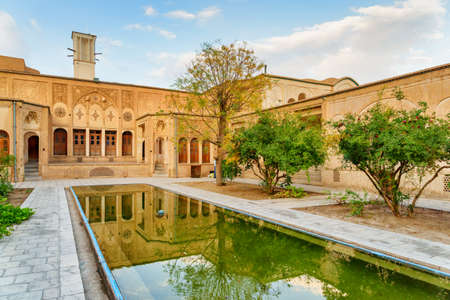 Wonderful view of the Borujerdi Historical House in Kashan, Iran. Traditional courtyard with garden and pool in the middle. Windcatcher (badgir) is visible on blue sky background. Persian architecture