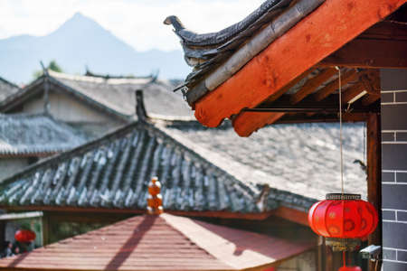 Traditional Chinese tile roof of house decorated with oriental red lantern in the Old Town of Lijiang, China. Others black roofs and mountains are visible in background. Focus on the lantern.