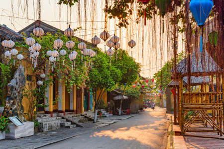 Awesome view of cozy street decorated with colorful silk lanterns at sunrise. Scenic traditional old yellow houses of Hoi An Ancient Town, Vietnam. Hoian is a popular tourist destination of Asia.