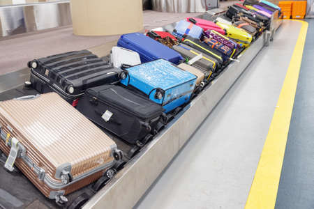 Multicolored suitcases and bags on luggage conveyor belt at arrival area of passenger terminal in airport. Baggage carousel.