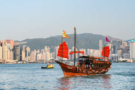 Hong Kong - October 21, 2017: Awesome view of traditional Chinese wooden sailing ship with red sails in Victoria harbor. High-rise residential buildings are visible at Hong Kong Island.