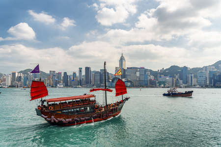 Hong Kong - October 20, 2017: Awesome view of traditional Chinese wooden sailing ship with red sails in Victoria harbor. Hong Kong Island skyline on sunny day. Amazing cityscape.