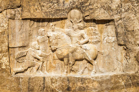 Wonderful bas-relief at ancient necropolis Naqsh-e Rustam in Iran. Detail of large tomb belonging to Achaemenid kings carved out of rock face at considerable height above the ground. Stock Photo