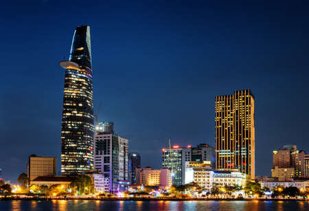 Ho Chi Minh City skyline and the Saigon River. Beautiful night view of skyscraper and other modern buildings at downtown. Ho Chi Minh City is a popular tourist destination of Vietnam. Scenic cityscape