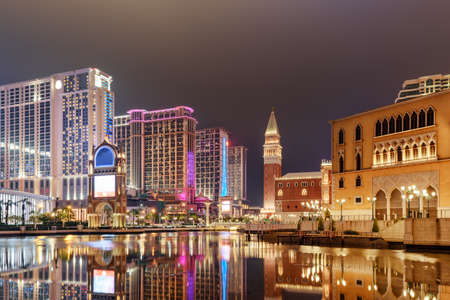 Amazing night view of hotels and casinos in Cotai of Macau. Scenic modern buildings reflected in water. Beautiful cityscape. Cotai is a new gambling and tourism area with casinos and shopping malls.