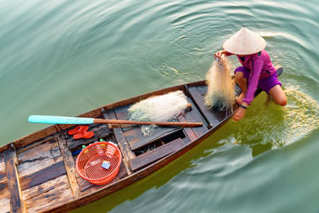 Closeup view of Vietnamese woman in traditional bamboo hat on wooden boat checking her fishing net on the Thu Bon River at Hoi An Ancient Town, Vietnam. Hoian is a popular tourist destination of Asia.