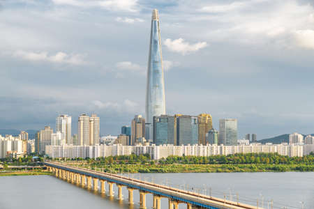 Amazing skyscraper at downtown of Seoul in South Korea on cloudy sky background. Scenic modern tower and Jamsil Railway Bridge over the Han River (Hangang). Wonderful cityscape.