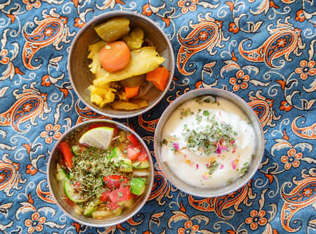 Wonderful top view of traditional Iranian snacks. Fresh vegetable salad, yogurt and pickled vegetables. Awesome Persian cuisine. 写真素材