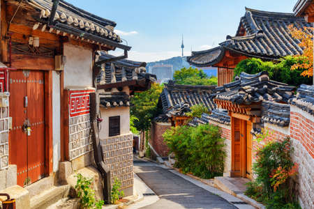 Gorgeous view of cozy old narrow street and traditional Korean houses of Bukchon Hanok Village in Seoul, South Korea. Seoul Tower on Namsan Mountain is visible on blue sky background. Scenic cityscape 스톡 콘텐츠 - 149895265