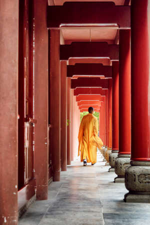 Buddhist monk walking along red wooden corridor of a monastery to a Chinese temple. Monk wearing yellow robe.