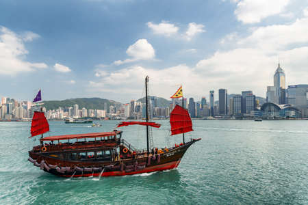 Hong Kong - October 20, 2017: Fabulous view of traditional Chinese wooden sailing ship with red sails in Victoria harbor. Hong Kong Island skyline on sunny day. Amazing cityscape.
