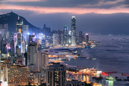 Fabulous aerial view of skyscrapers in downtown of Hong Kong and Victoria Harbor at sunset. Awesome cityscape. Hong Kong is a popular tourist destination of Asia.