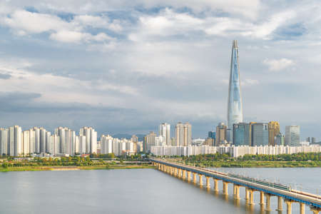 Amazing view of skyscraper at downtown of Seoul in South Korea on cloudy sky background. Scenic modern tower and Jamsil Railway Bridge over the Han River (Hangang). Wonderful cityscape. Reklamní fotografie