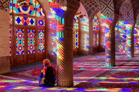 Shiraz, Iran - 31 October, 2018: Colorful morning view of prayer hall at the Nasir al-Mulk Mosque (Pink Mosque). Sunlight reflected through stained glass windows on columns, the wall and the floor.