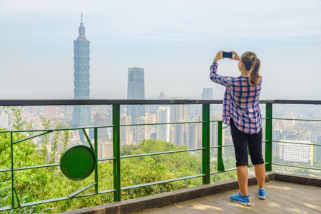 Female tourist taking pictures and enjoying scenic view of Taipei from top of mountain. Awesome Taipei skyline, Taiwan. Wonderful cityscape. Skyscrapers and other modern buildings of downtown.