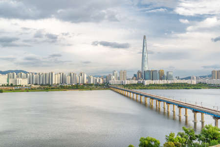 Scenic view of Jamsil Railway Bridge over the Han River (Hangang) at downtown of Seoul in South Korea. Skyscraper is visible on cloudy sky background. Wonderful cityscape.