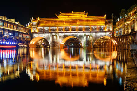Colorful night view of the Hong Bridge (Rainbow Bridge) over the Tuojiang River (Tuo Jiang River) in Phoenix Ancient Town (Fenghuang County), China. Fenghuang is a popular tourist destination of Asia.