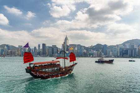 Hong Kong - October 20, 2017: Traditional Chinese wooden sailing ship with red sails crossing Victoria harbor. Hong Kong Island skyline. Amazing cityscape.