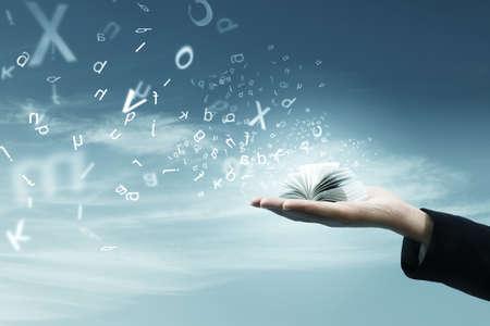 volar: Libro de magia en la mano