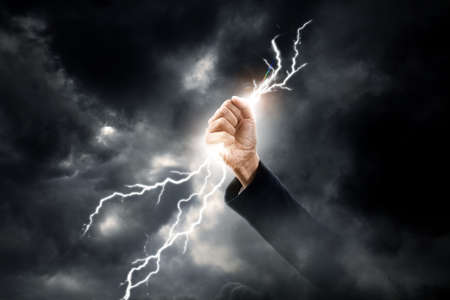 lightning storm: business woman hand clenching lightning flash Stock Photo