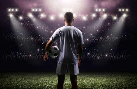 スタジアムにボールを持つフットボール選手 写真素材