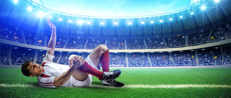 Injured football player on stadium field. The imaginary football stadium is modeled and rendered. Stock Photo
