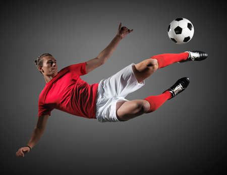 Soccer player in action on black background.