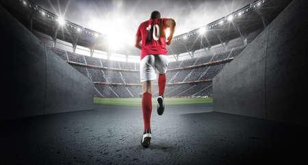 Soccer player entering the 3d imaginary stadium.The imaginary soccer stadium is modeled and rendered.