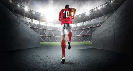 Soccer player entering the 3d imaginary stadium.The imaginary soccer stadium is modeled and rendered.