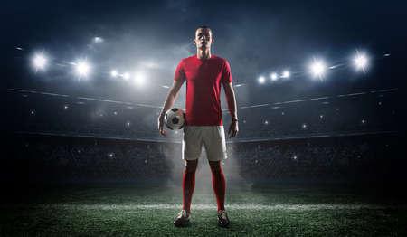 Jugador de fútbol en el fondo del estadio. El estadio de fútbol imaginario está modelado y renderizado.