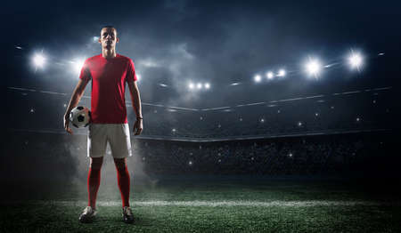 Soccer player in action on stadium background.The imaginary football stadium is modeled and rendered.