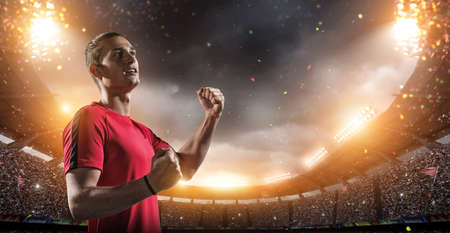 Happy soccer player with a goal joy in the 3d imaginary stadium background.The imaginary soccer stadium is modeled and rendered. Standard-Bild