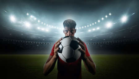 Joueur de football avec les lumières du stade