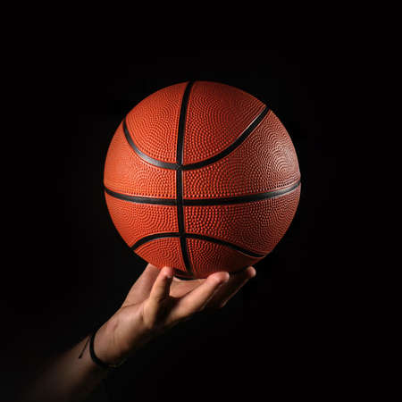 Basketball and hand, black background Foto de archivo