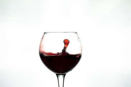 Red wine splash into glass on white background.