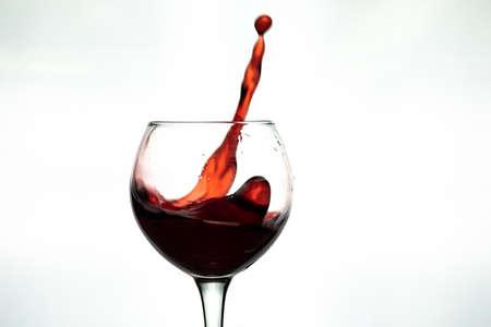 Red wine splash into glass on white background.