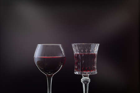 Rose wine. Red wine in two wine glasses over dark background with rays of light.