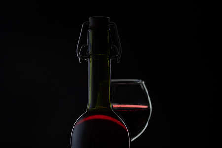 Wine. Red wine in wine glass over dark background. Silhouette of bottle with rose wine and opener on cork Imagens