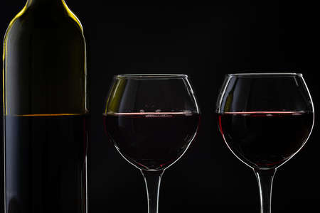 Wine. Red wine in two wine glasses over dark background. Silhouette of bottle with rose wine Standard-Bild