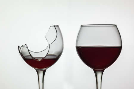 Broken and not broken wine glass with red wine on white background.