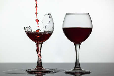Wine. Red wine pouring into broken wine glass on the wet surface. Rose wine pour. Close up shot. White background