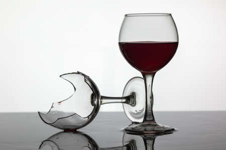 Filled with a glass of wine and broken wine glass with red wine which is laying on the wet surface. White background Imagens