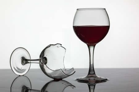 Lleno de una copa de vino y copa de vino rota con vino tinto que está sobre la superficie húmeda. Fondo blanco