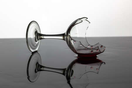 Broken wine glass with red wine which is laying on the wet surface. White background