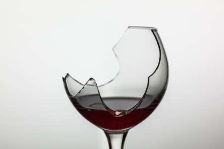 Broken wine glass with red wine on white background.
